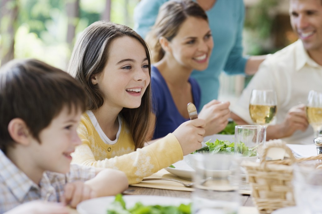 Family eating dinner together --- Image by © Laura Doss/Corbis